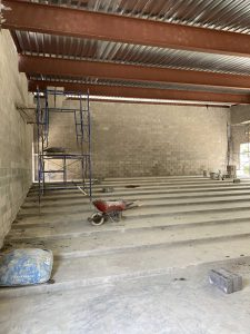 Photo of the interior of Library's new Community Room addition under construction, showing the tiered concrete floor.