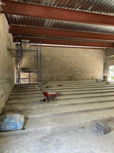 Thumbnail photo of the interior of Library's new Community Room addition under construction showing the tiered concrete floor.