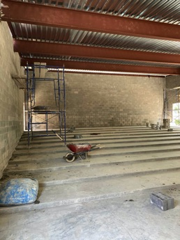 Thumbnail photo of the interior of Library's new Community Room addition under construction, showing the tiered concrete floor.